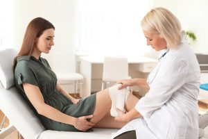 Doctor applying bandage to patient's knee in clinic